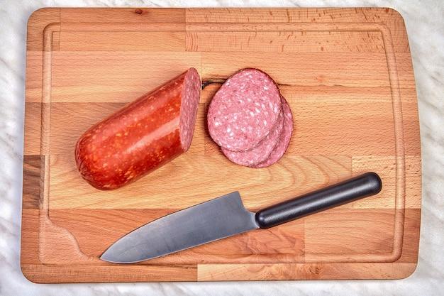 Pedaços de linguiça picada e faca de cozinha encontram-se na tábua de madeira.