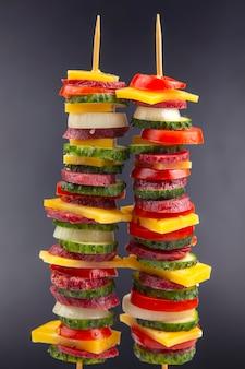Pedaços de linguiça, salame, queijo, pepino e tomate. comida rápida. ingredientes para pizza. calorias e dieta