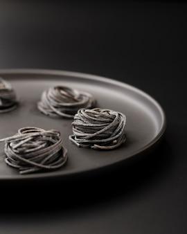 Pedaços de macarrão em um prato escuro sobre um fundo escuro