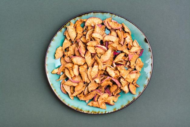 Pedaços de maçãs secas em um prato sobre um fundo verde. alimentação saudável. vista do topo