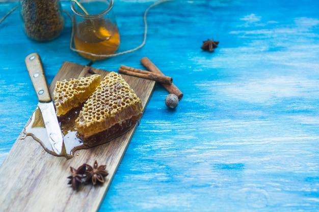 Pedaços de mel com especiarias; jarra de pólen de abelha; faca e pote de mel no pano de fundo azul