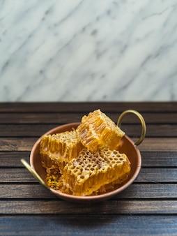 Pedaços de mel de pente fresco em utensílio de cobre na mesa de madeira