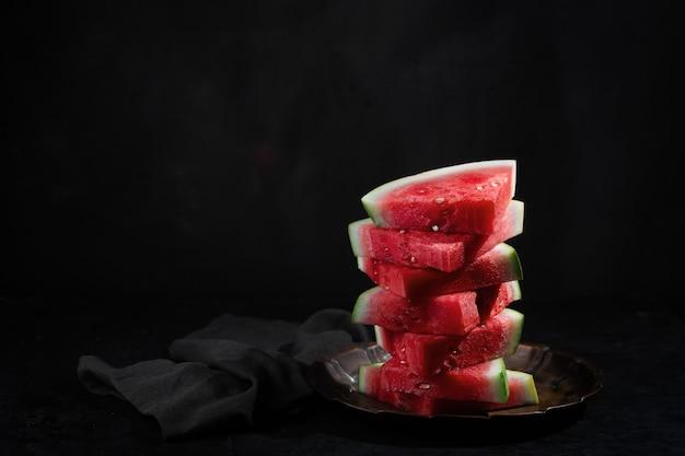 Pedaços de melancia crua vermelha em fundo escuro com espaço de cópia. é uma polpa doce e suculenta, geralmente de um vermelho profundo a rosa, com muitas sementes pretas, embora existam variedades sem sementes
