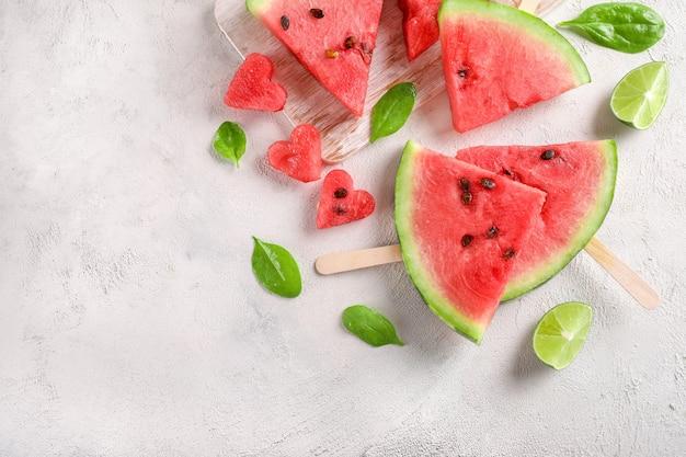 Pedaços de melancia em palitos em fundo branco. vista do topo. copie o espaço.
