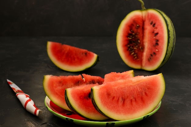Pedaços de melancia suculenta estão localizados em um prato sobre um fundo escuro. também há uma faca na mesa. foto horizontal.