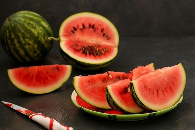 Pedaços de melancia suculenta estão localizados em um prato sobre um fundo escuro