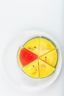 Pedaços de melancia vermelha e amarela em um prato redondo branco