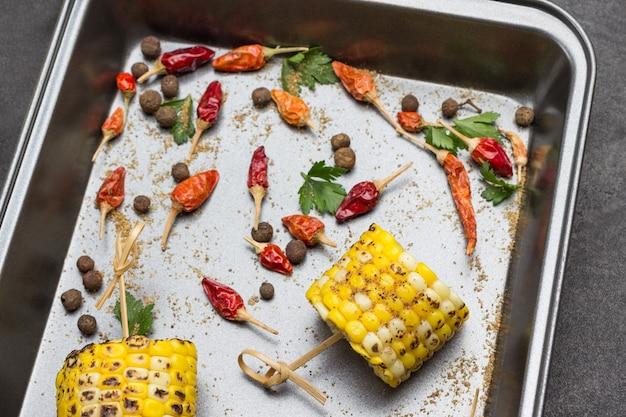 Pedaços de milho grelhado em espetos na bandeja. vagens secas de pimenta vermelha. vista do topo