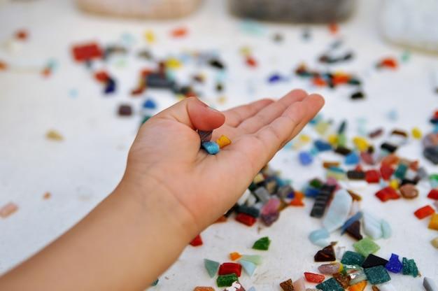 Pedaços de mosaico de vidro colorido na mão da criança em cima da mesa