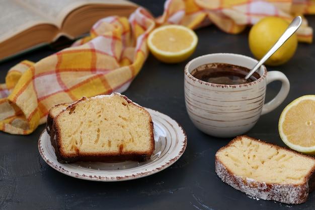 Pedaços de muffin de limão dispostos em um prato contra um fundo escuro com uma xícara de café ao fundo