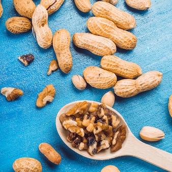 Pedaços de noz na colher de pau com amendoim e pistache sobre fundo azul
