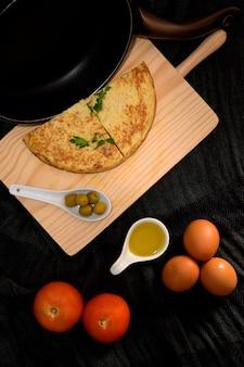 Pedaços de omelete na mesa de cozinha de madeira com azeitonas, gema de ovo, tomate e ovos frescos nas laterais