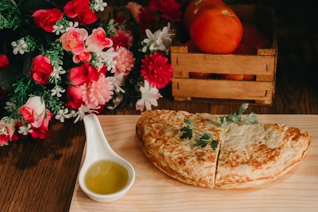 Pedaços de omelete na mesa de madeira com óleo, tomate e um buquê de flores nas laterais