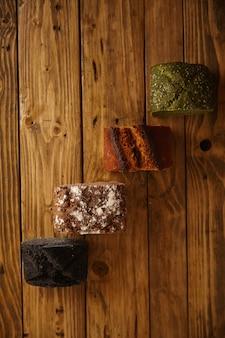 Pedaços de pães caseiros misturados apresentados em mesa de madeira como amostras para venda: pistache