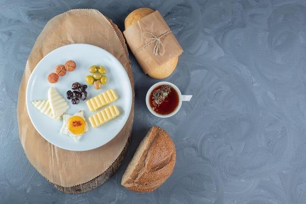Pedaços de pão ao lado de uma xícara de chá, um copo de suco e uma travessa de queijo, ovo, manteiga e fatias de salsicha em uma placa de madeira sobre a mesa de mármore.