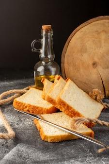 Pedaços de pão branco fatiados e saborosos isolados com cordas e óleo na vista frontal