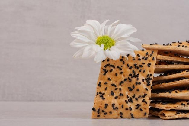 Pedaços de pão crocante com sementes de gergelim preto na mesa branca com flores.