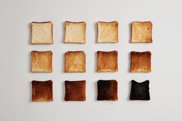 Pedaços de pão dourados como resultado da torragem. deliciosas fatias de pão tenras de crosta preparadas em torradeira que podem ser servidas com patês ou recheios, isoladas sobre superfície branca. estágios de queima.