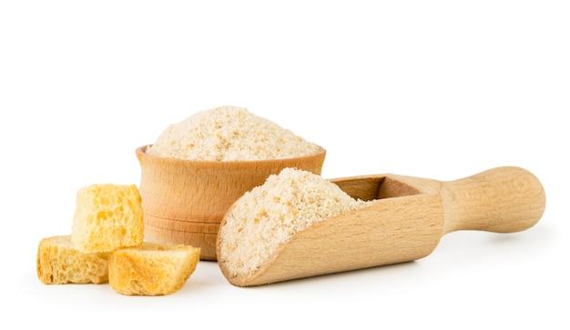 Pedaços de pão seco e pão ralado em uma tigela de madeira e colher