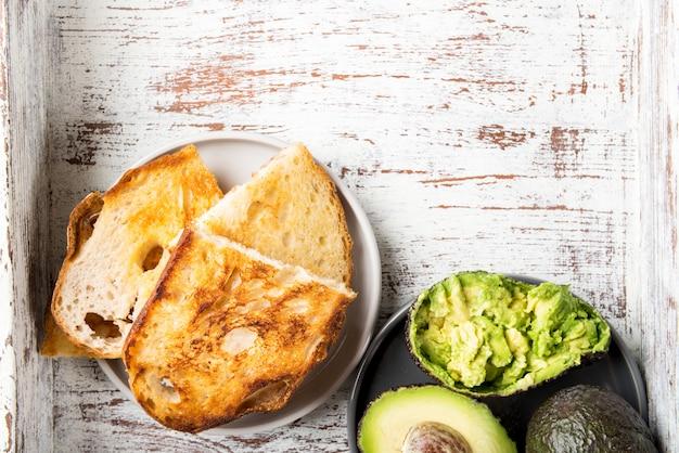 Pedaços de pão torrado branco e abacate maduro