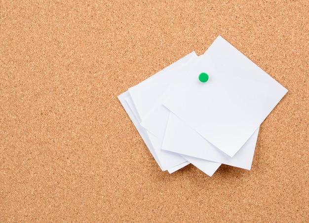 Pedaços de papel em branco, quadrados e brancos fixados em uma placa de cortiça, copie o espaço