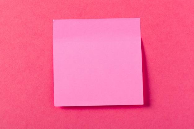 Pedaços de papel em branco sobre um fundo rosa colorido