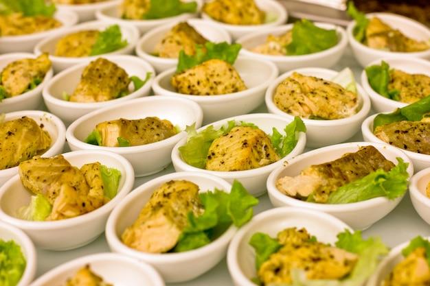 Pedaços de peixe branco grelhados, servidos em taças brancas, decorados com folhas de alface