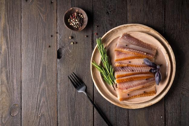 Pedaços de peixe defumado e abacate em um prato sobre um fundo escuro de madeira