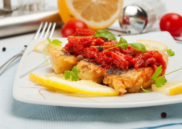 Pedaços de peixe frito com marinada de legumes.