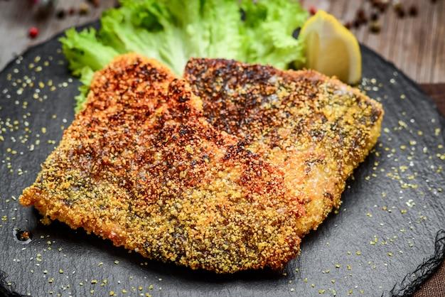 Pedaços de peixe frito em um prato de cerâmica sobre uma superfície de madeira escura