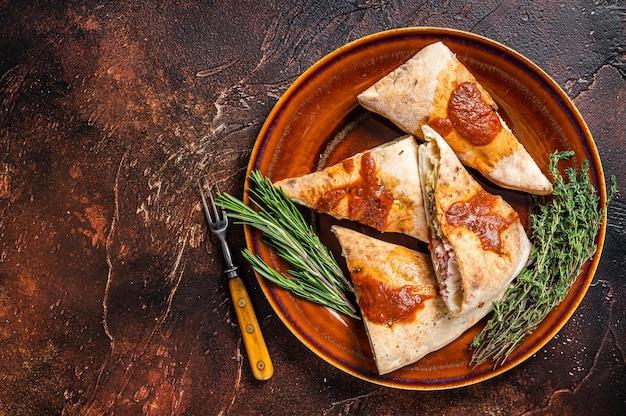 Pedaços de pizza calzone em prato rústico com molho de tomate e ervas. fundo escuro. vista do topo. copie o espaço.