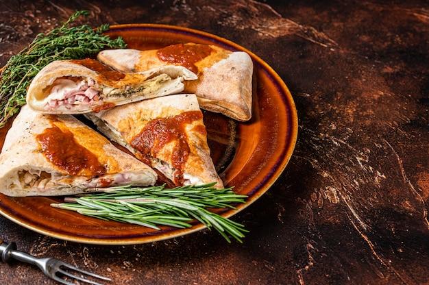 Pedaços de pizza calzone em prato rústico com molho de tomate e ervas