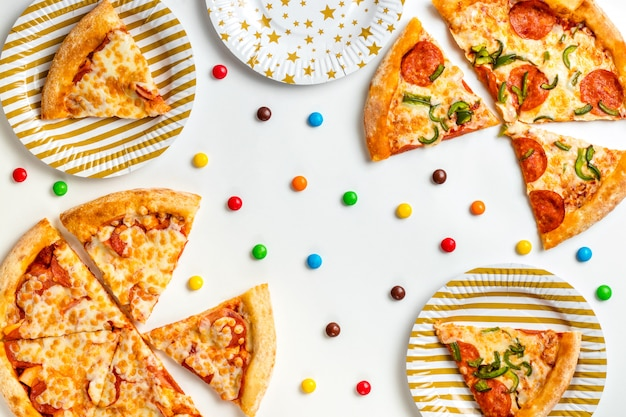 Pedaços de pizza e doces coloridos em um fundo branco. aniversário com junk food. festa infantil. vista superior com espaço de cópia de texto. configuração plana