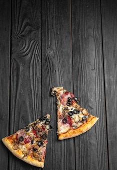 Pedaços de pizza na tábua de madeira escura, tradicional pizza italiana