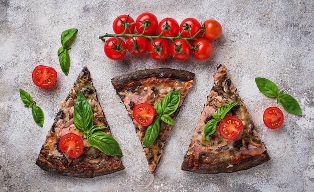 Pedaços de pizza preta com tomate e manjericão