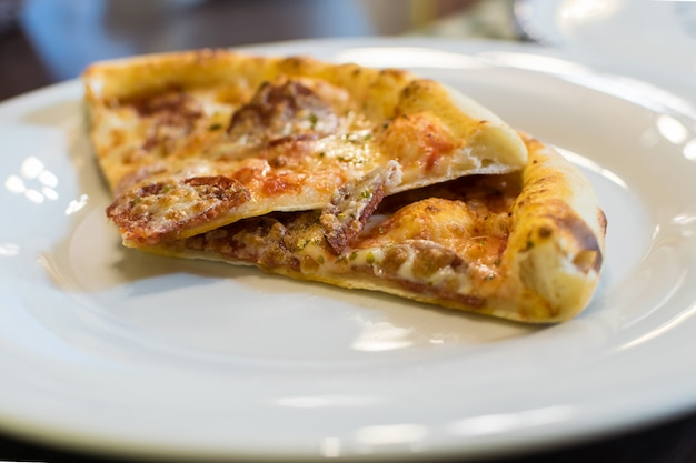 Pedaços de pizza quente fresca com salsicha de calabresa e queijo mussarela polvilhado com ervas. foco seletivo