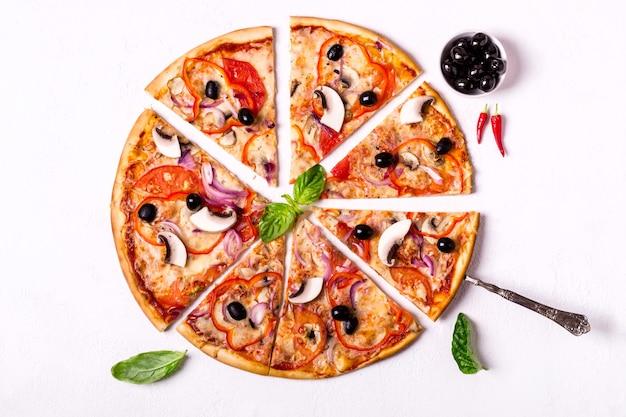 Pedaços de pizza vegetariana com cogumelos e azeitonas em fundo branco.