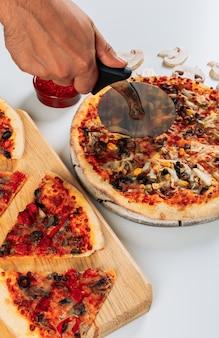 Pedaços de pizzas em uma tábua de pizza com especiarias, fatias picadas de cogumelos e uma cortadora de pizza, vista de alto ângulo sobre um fundo azul claro