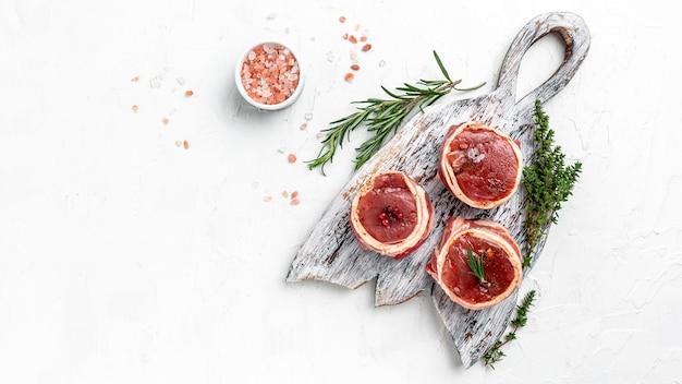 Pedaços de porco frescos prontos para cozinhar. bifes de medalhões do lombo embrulhados em bacon na placa de woden sobre um fundo claro, filé mignon. vista do topo.