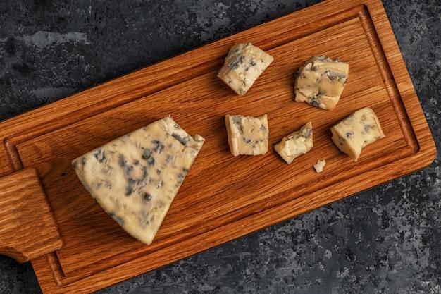 Pedaços de queijo azul na tábua de servir de madeira