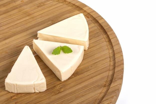 Pedaços de queijo cremoso triangular com hortelã em uma placa de madeira isolada em uma mesa branca