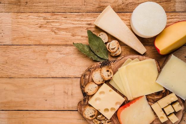 Pedaços de queijo diversos; folhas de louro e fatias de pão na mesa de madeira
