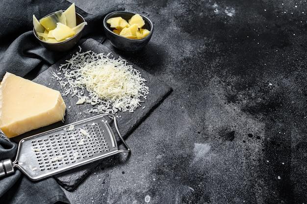 Pedaços de queijo duro parmigiano reggiano. fatia, corte, ralado. fundo preto. vista do topo. copie o espaço
