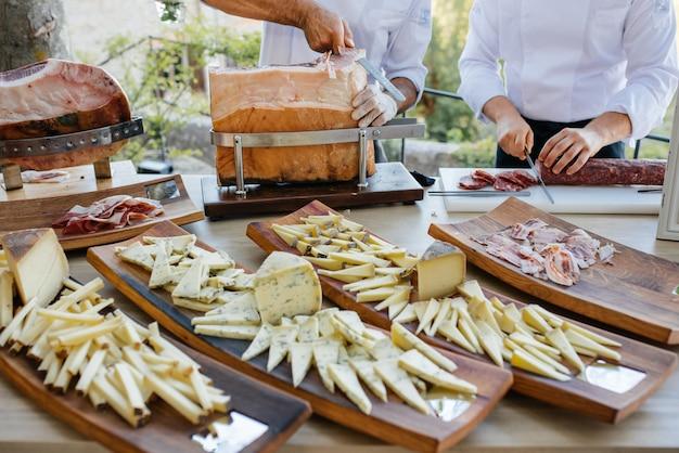 Pedaços de queijo e faca com alça laranja mentem na placa de madeira