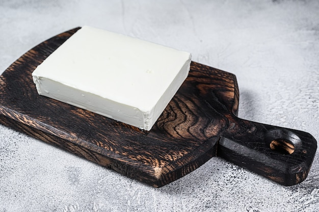 Pedaços de queijo fresco paneer em uma placa de corte.