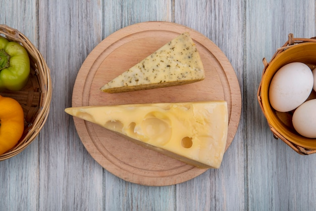 Pedaços de queijo holandês em um suporte com pimentões e ovos de galinha em um fundo cinza.
