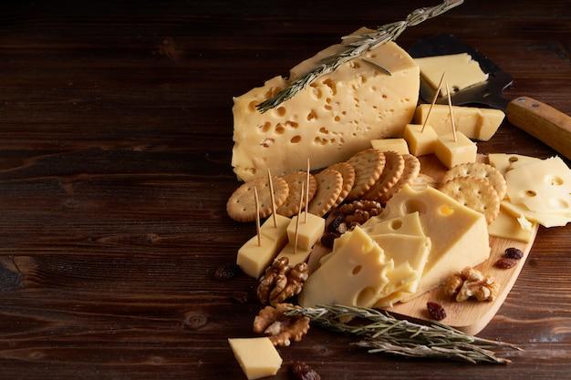 Pedaços de queijo, nozes, passas, lanches para o vinho. espaço de cópia apetitiva