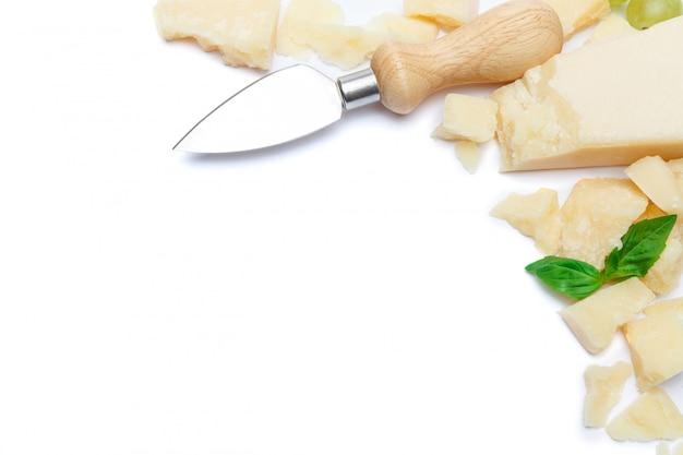 Pedaços de queijo parmesão e faca na mesa branca