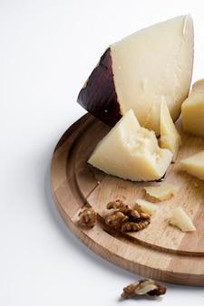 Pedaços de queijo parmesão jugas em uma placa de madeira