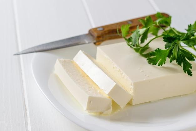 Pedaços de queijo sérvio com uma faca e salsa em uma mesa branca. a vista do topo. produto lácteo.